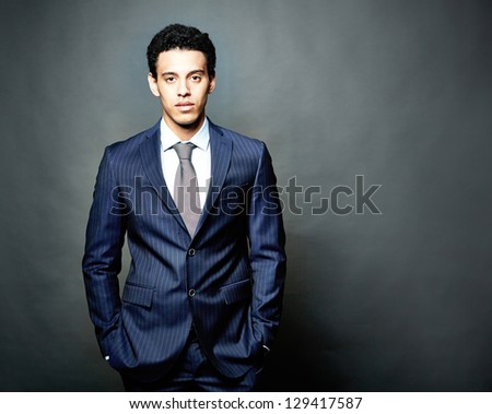 Portrait of confident man in suit looking at camera over grey background - stock photo