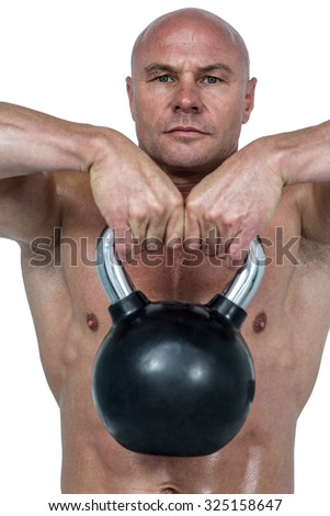 Portrait of confident man lifting kettlebell against white background - stock photo