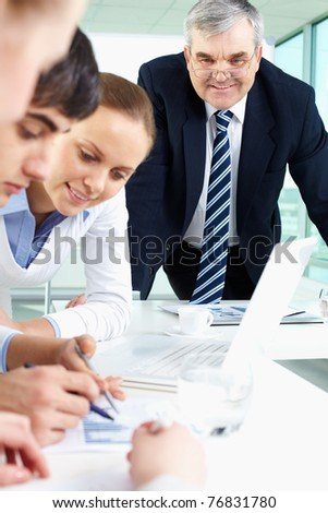 Portrait of confident man looking at document being discussed by co-workers - stock photo