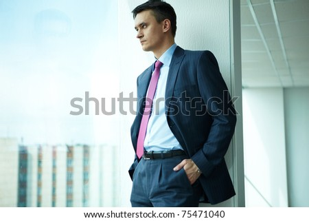 Portrait of confident man looking through window in office - stock photo