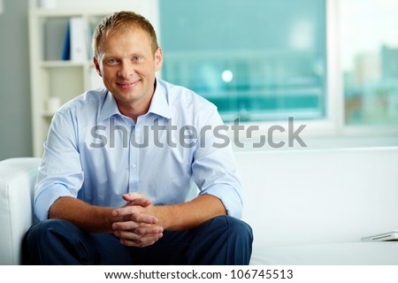 Portrait of confident man sitting in office - stock photo