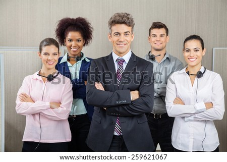 Portrait of confident manager and team standing arms crossed at call center - stock photo