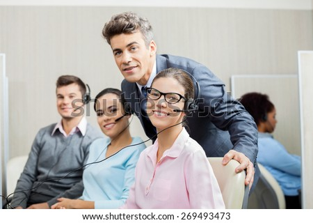 Portrait of confident manager with team in call center - stock photo