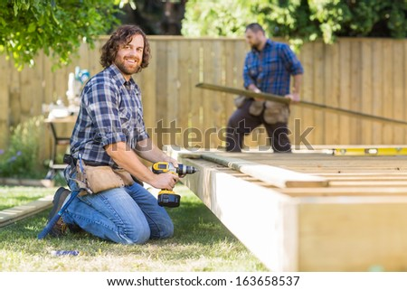 Portrait of confident manual worker drilling wood with coworker working in background at construction site - stock photo