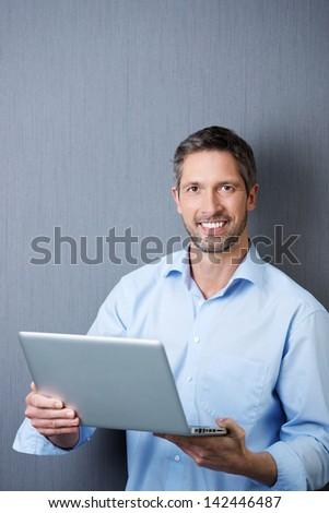 Portrait of confident mature businessman holding laptop against blue wall - stock photo