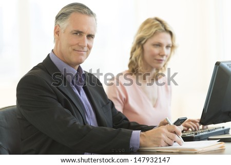 Portrait of confident mature businessman holding pen and mobile phone with female colleague using computer in office - stock photo
