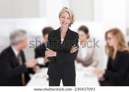 Portrait of confident mature businesswoman standing arms crossed against colleagues in boardroom - stock photo
