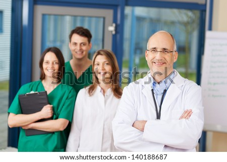 Portrait of confident mature male doctor with team in background at clinic - stock photo