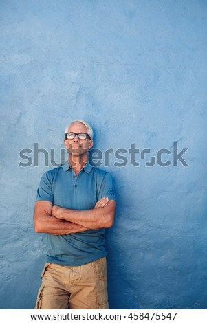 Portrait of confident mature man standing against a blue background. Handsome  male in glasses standing with his arms crossed and looking up at copy space on a wall. - stock photo