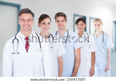 Portrait of confident medical team standing in row at hospital - stock photo