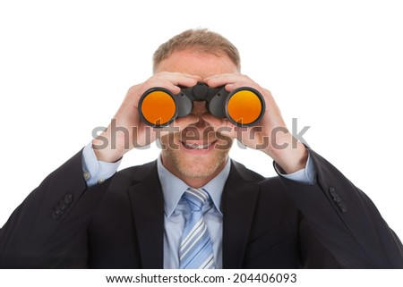 Portrait of confident mid adult businessman looking through binoculars over white background - stock photo