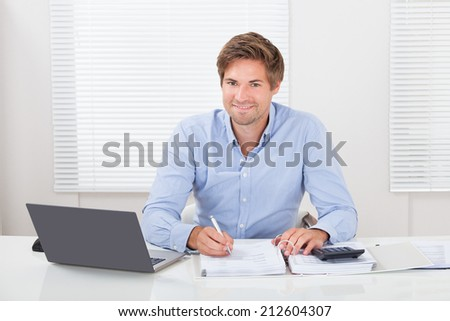 Portrait of confident mid adult businessman working at desk in office - stock photo