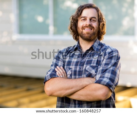 Portrait of confident mid adult carpenter with arms crossed standing at construction site - stock photo