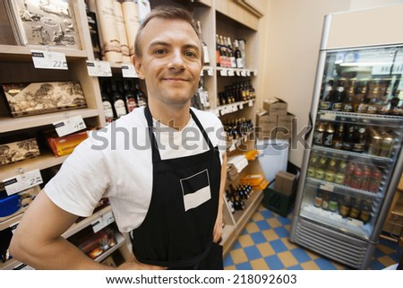 Portrait of confident mid adult salesman standing hands on hips in grocery store - stock photo