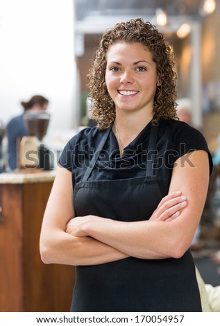 Portrait of confident mid adult waitress standing arms crossed in cafeteria - stock photo