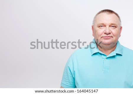 Portrait of confident middle aged man in blue shirt over white background - stock photo
