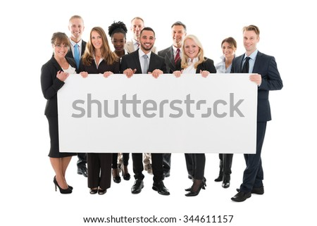 Portrait of confident multi ethnic business team holding blank billboard against white background - stock photo