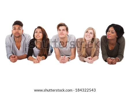 Portrait of confident multiethnic college students lying over white background - stock photo
