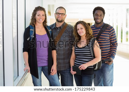 Portrait of confident multiethnic university students with digital tablets standing at corridor - stock photo