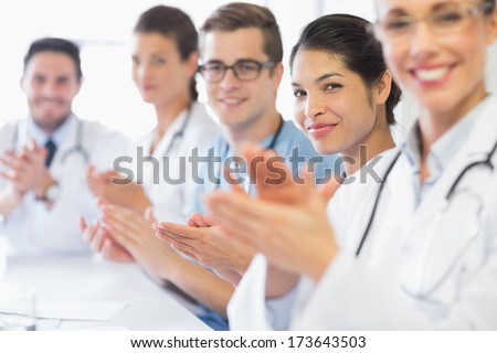 Portrait of confident nurse and doctors applauding in hospital - stock photo