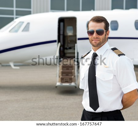 Portrait of confident pilot wearing sunglasses with private jet in background - stock photo