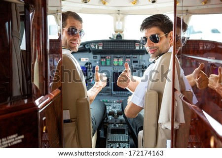 Portrait of confident pilots gesturing thumbs up in cockpit of private jet - stock photo