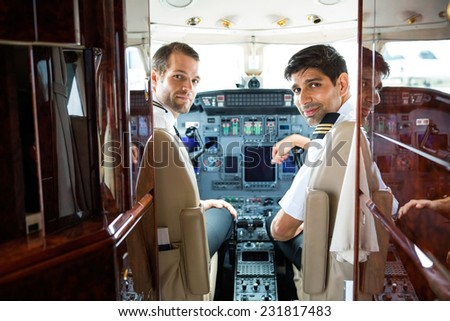 Portrait of confident pilots in corporate plane cockpit - stock photo