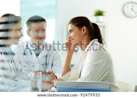 Portrait of confident practitioners consulting patient in hospital - stock photo