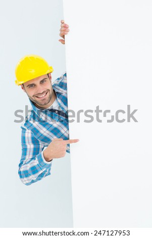 Portrait of confident repairman pointing at blank billboard on white background - stock photo