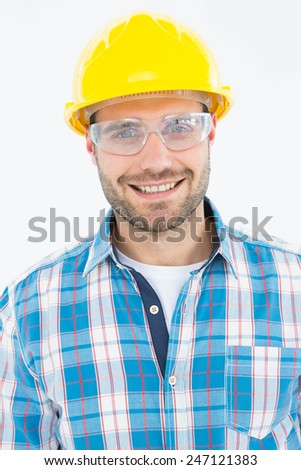 Portrait of confident repairman wearing protective glasses on white background - stock photo