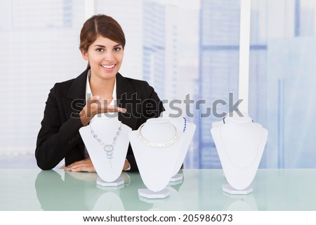 Portrait of confident saleswoman displaying jewelry at desk in office - stock photo