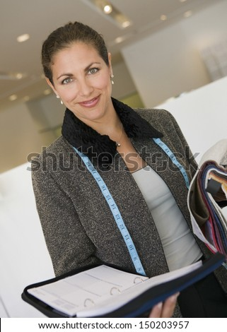 Portrait of confident saleswoman with fabric swatches and daily planner in furniture store - stock photo
