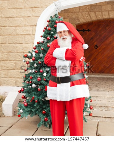 Portrait of confident Santa Claus standing arms crossed outside house - stock photo