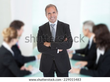 Portrait of confident senior businessman standing arms crossed against colleagues in boardroom - stock photo