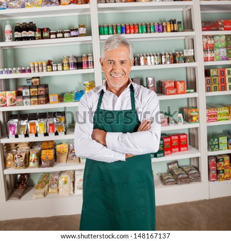 Portrait of confident senior male owner smiling in supermarket - stock photo