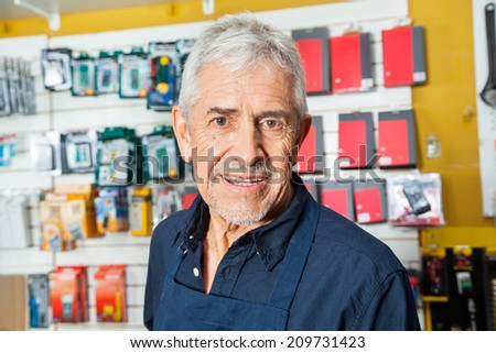 Portrait of confident senior worker smiling in hardware shop - stock photo