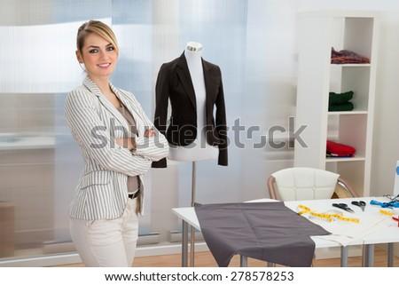 Portrait Of Confident Smiling Fashion Designer In Studio - stock photo