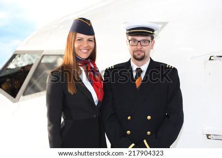 Portrait of confident stewardess and pilot standing against plane. - stock photo