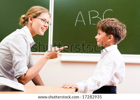 Portrait of confident teacher explaining grammar to schoolchild who looking at her attentively - stock photo
