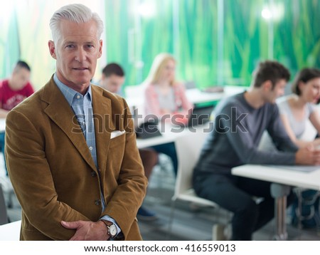 portrait of confident teacher in school classroom,  students group on class in background - stock photo