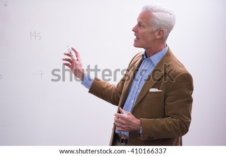 portrait of confident teacher solving problems on whiteboard in classroom - stock photo