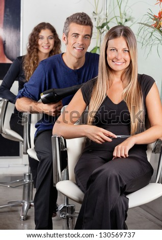 Portrait of confident team of hairdressers sitting at hair salon - stock photo
