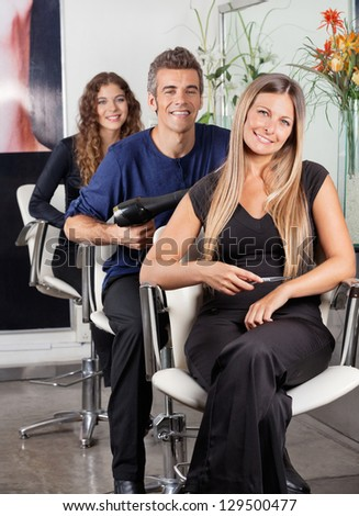 Portrait of confident team of hairstylists sitting at beauty parlor - stock photo
