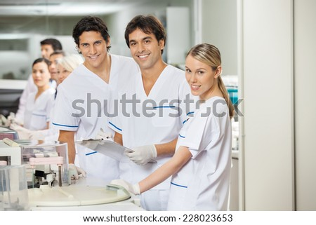 Portrait of confident team of researchers in laboratory - stock photo