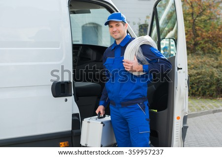 Portrait of confident technician with cable coil and toolbox standing outside van - stock photo