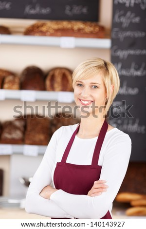 Portrait of confident waitress with arms crossed standing in bakery - stock photo