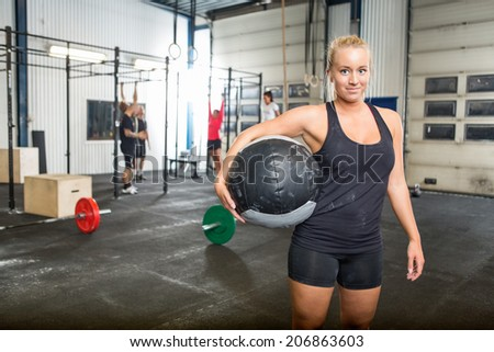 Portrait of confident woman carrying medicine ball in gym - stock photo