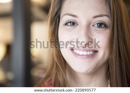 Portrait of confident woman smiling in cafe - stock photo