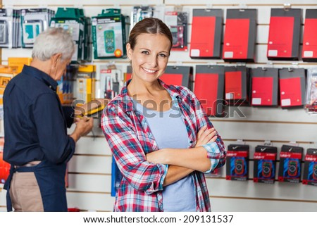 Portrait of confident woman with arms crossed standing against worker in hardware store - stock photo