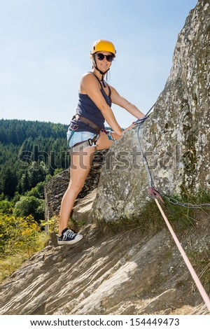 Portrait of confident woman with climbing equipment standing on rock - stock photo